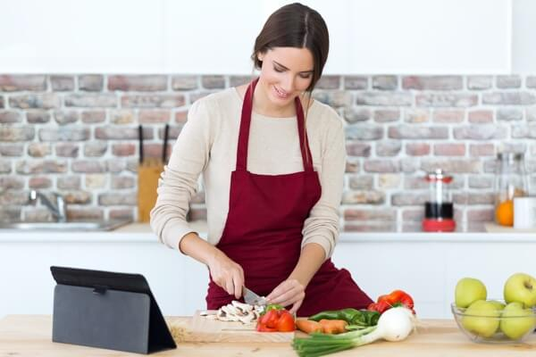 Plant Based Kidneys recipes with young woman with dark red apron cutting up vegetables on cutting board in kitchen